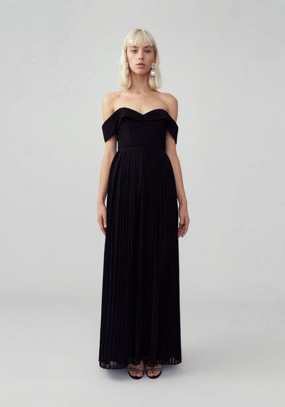 Woman in black pleated off shoulder dress front.