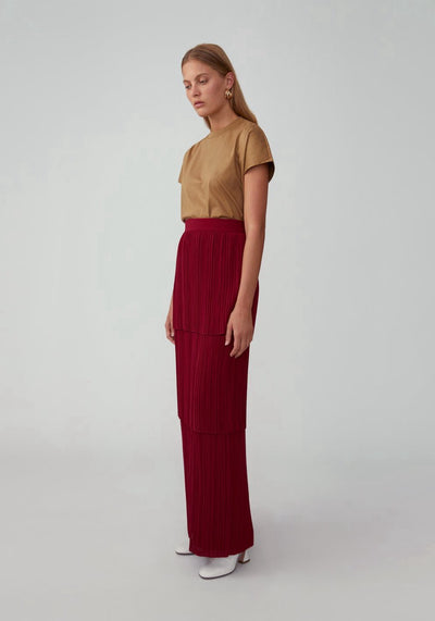 Woman in red high waist maxi pleated skirt front.