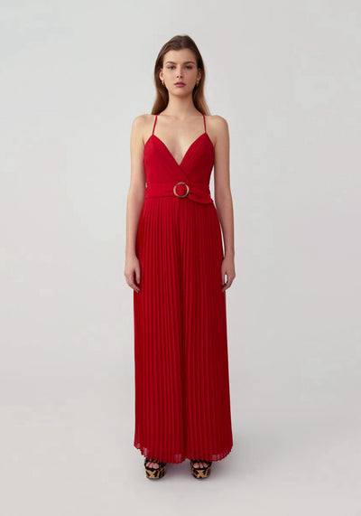 Woman in red pleated jumpsuit front.