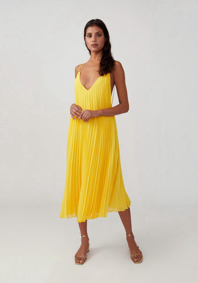 Woman in dandelion loose fitted pleated dress front.