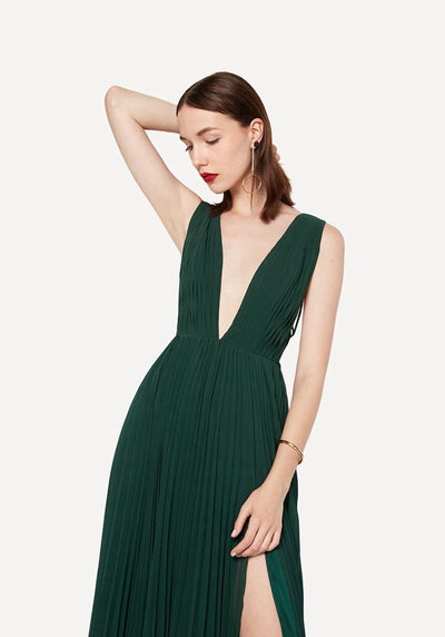 Woman in forest green deep v neck pleated dress front.