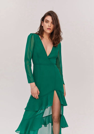 Woman in emerald green long sleeve ruffle dress front.