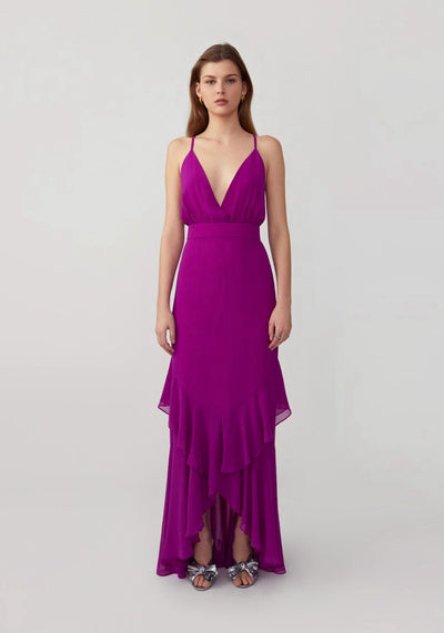 Woman in magenta high-low ruffle dress front.