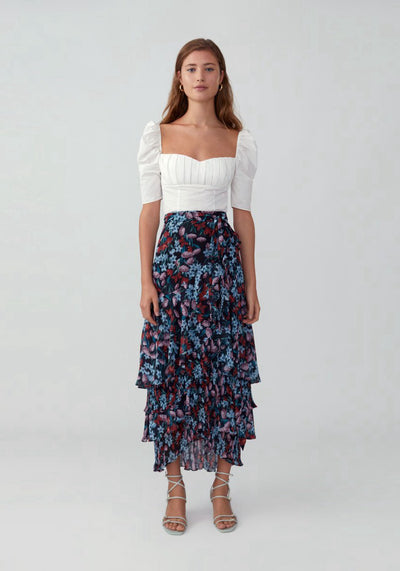 Woman in meadow floral black ruffled wrap skirt front.