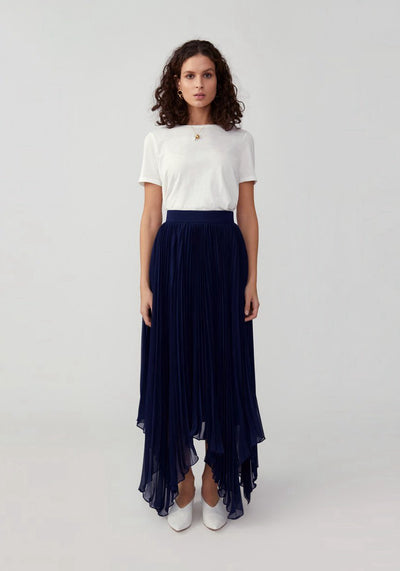 Woman in navy pleated asymmetrical  skirt front.