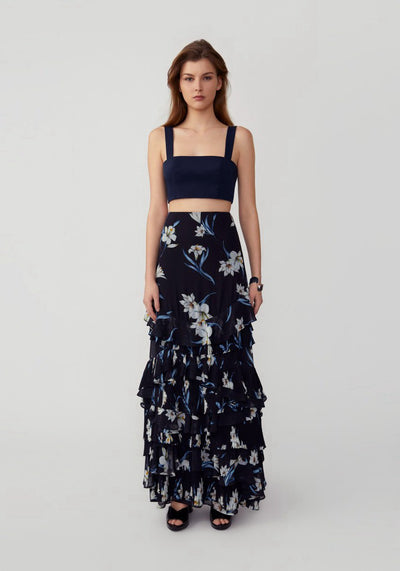 Woman in night lily black ruffled and pleated skirt front.