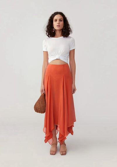 Woman in orange fit and flare asymmetrical skirt front.