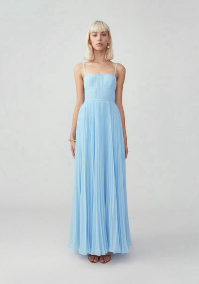 Woman in pale blue pleated maxi dress front.