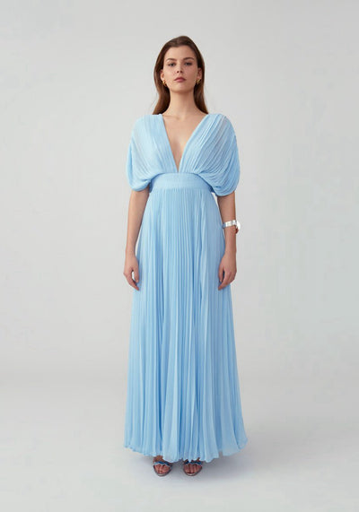Woman in pale blue draped pleated dress front.