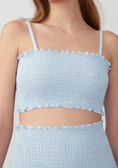 Woman in pale blue smocked two piece front.