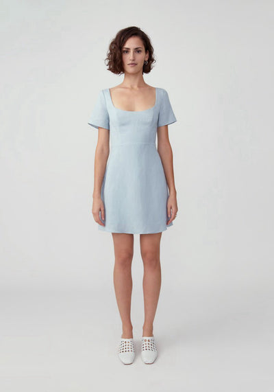 Woman in pale blue scoop neck mini skirt dress front.