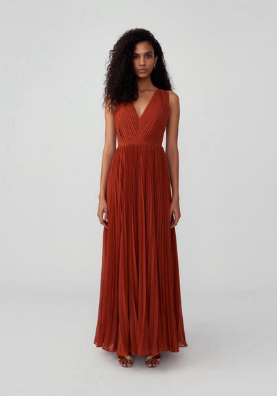 Woman in red ochre pleated maxi dress front.