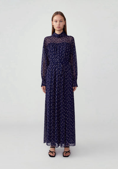 Woman in blue polka dot high neck maxi dress front.