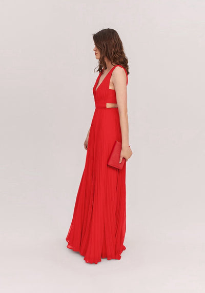 Woman in red deep v neckline pleated dress side.