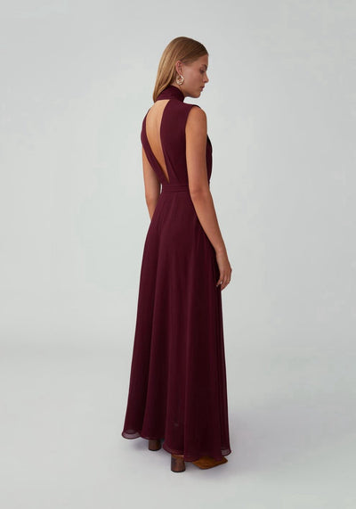 Woman in burgundy plunging v back dress back.