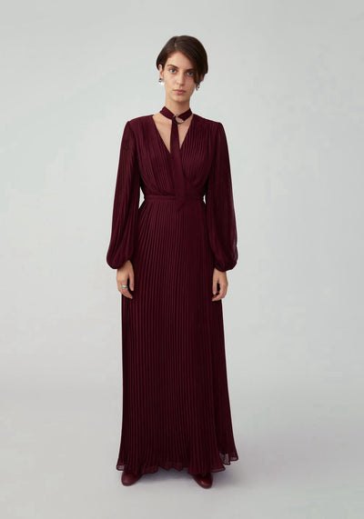 Woman in wine long sleeve pleated dress with neck tie front.