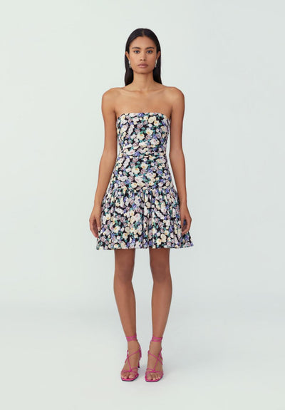 Woman in floral blossom black dropped waist strapless dress front.