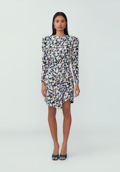 Woman in floral blossom black long puff sleeve asymmetrical mini dress front.