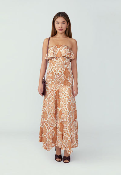 Woman in python rust strapless dress front.