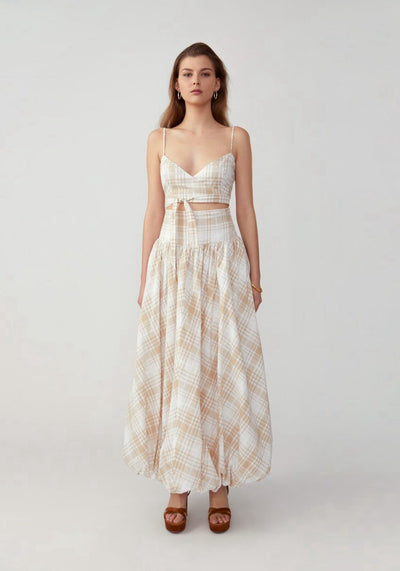 Woman in plaid light nude wrap top and bubble hem skirt set front.
