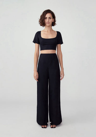 Woman in black two piece pant set front.