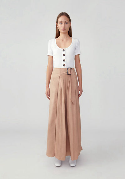 Woman in dark nude pleated belted skirt front.