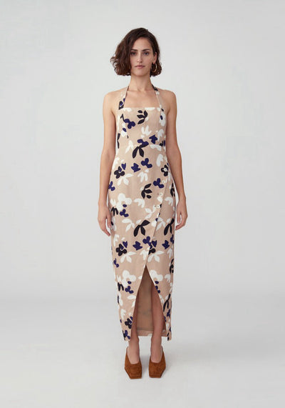 Woman in tan printed floral halter asymmetrical dress front.