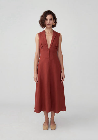 Woman in red ochre v neck button front petti dress front.