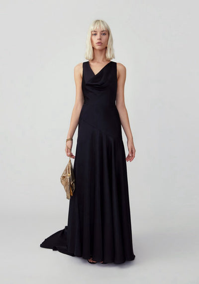 Woman in black asymmetrical cowl neckline dress with train front.