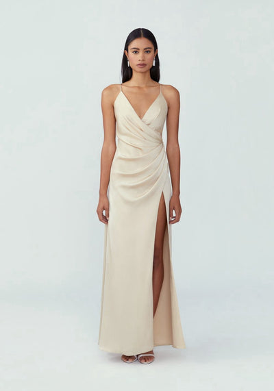 Woman in champagne low neckline with draping across the bodice dress front.