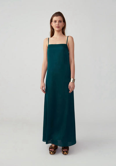 Woman in dark forest A Line maxi dress front.