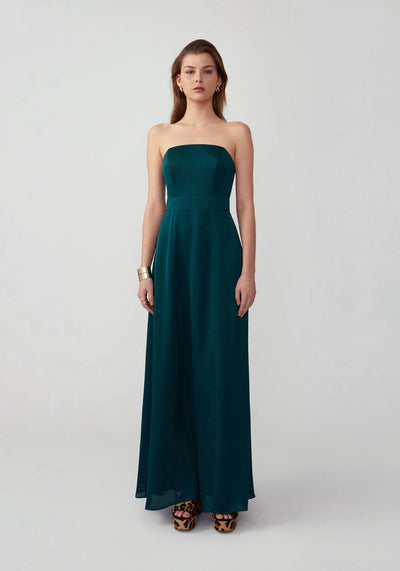 Woman in dark forest strapless dress front.