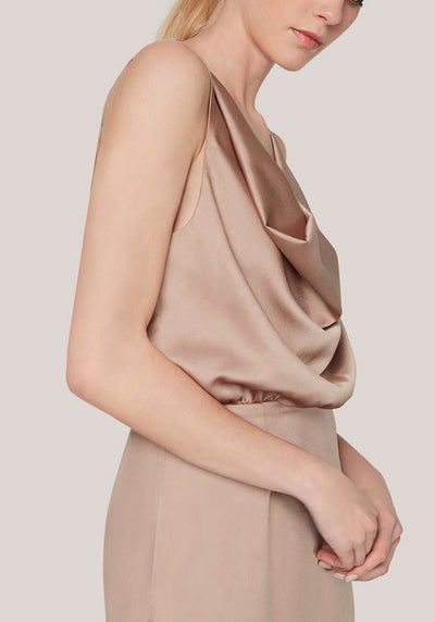Woman in dark nude cowl neck dress side.