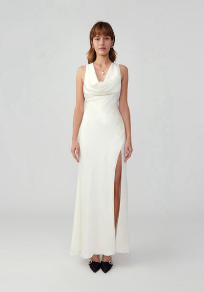 Woman in ivory drape with slit dress front.