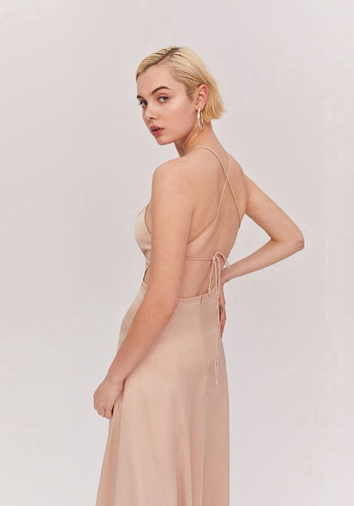 Woman in light nude tie back dress back.