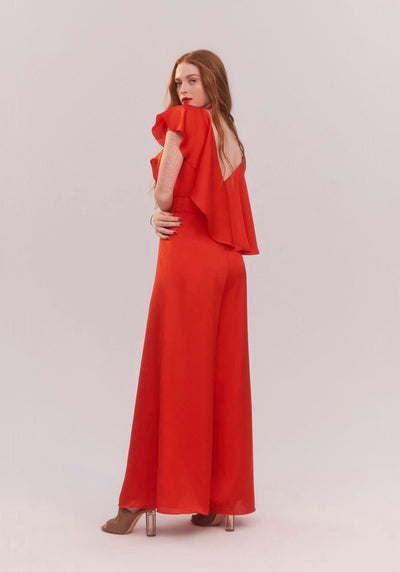 Woman in red ruffle top jumpsuit back.