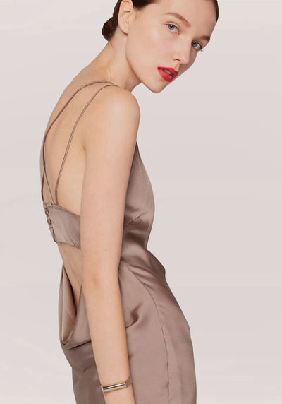 Woman in taupe slip dress side.