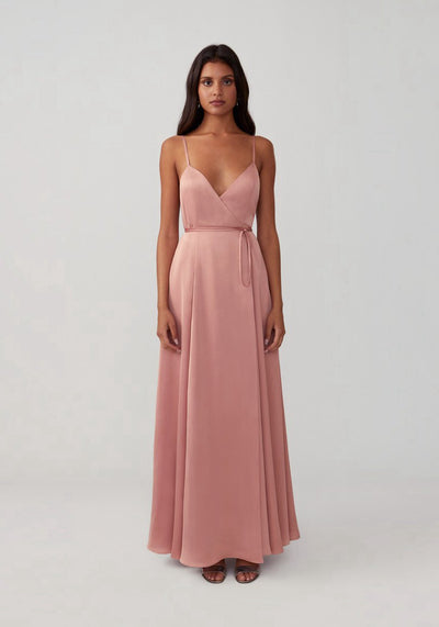 Woman in blush V-neck cross back wrap dress front.