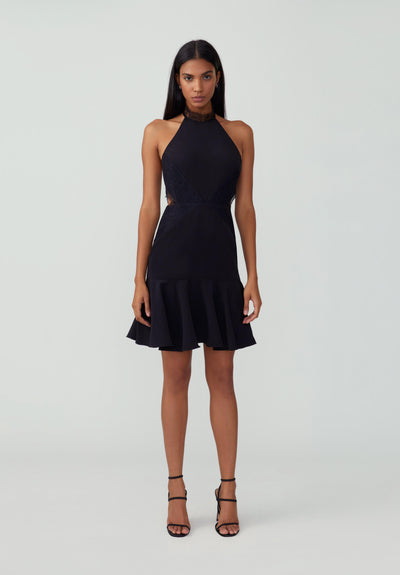 Women in black halter ruffle hem dress front.