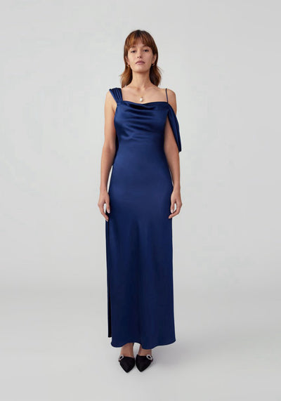 Woman in navy drape dress front.