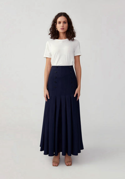 Woman in navy full pleated skirt front.