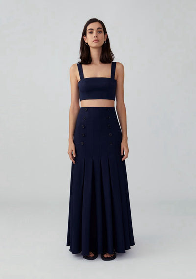 Woman in navy two piece pleated skirt front.