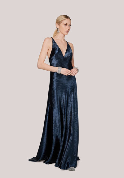 Woman in metallic navy plunging neckline dress front.