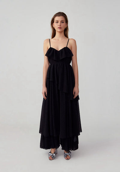 Woman in black asymmetrical dress front.