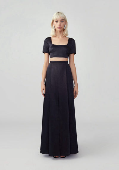 Woman in black fitted two piece dress front.