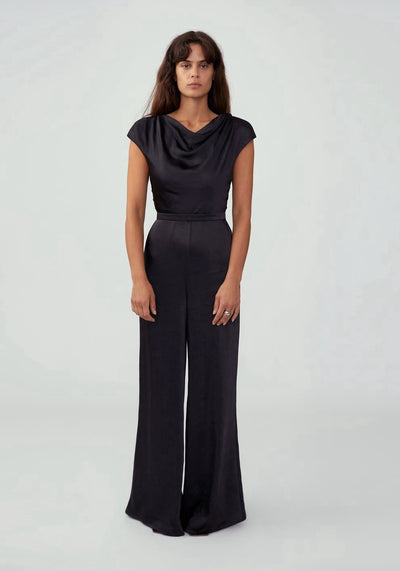 Woman in black cowl neck sleeved jumpsuit front.