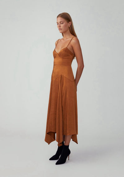 Woman in butterscotch asymmetrical dress side.