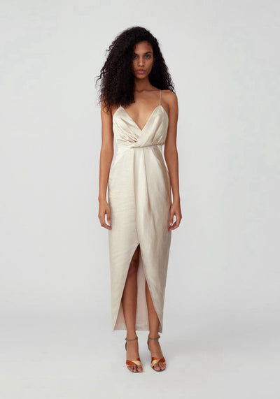 Woman in champagne asymmetrical drape dress front.