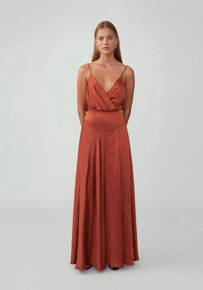 Woman in red ochre draped backless dress front.