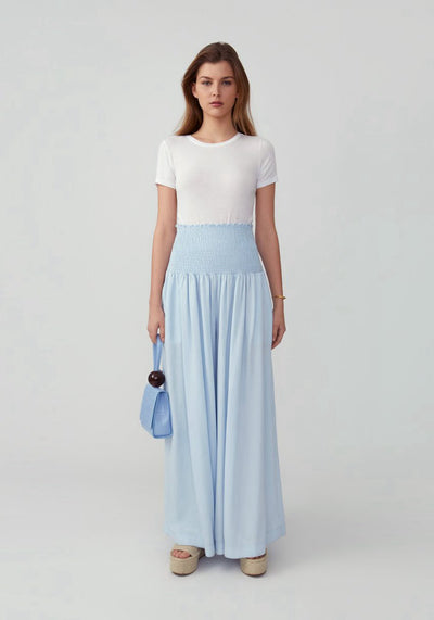 Woman in pale blue smocked waist wide leg pant front.